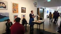A woman in a gallery space reading while standing at a desk
